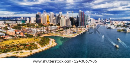 New modern urban developmen Barangaroo on shores of Sydney Harbour in Sydney city CBD under cloudy sky in aerial panorama over waters of Darling harbour. Royalty-Free Stock Photo #1243067986