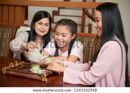 Group of Asian adult women and teenage girl having tea ceremony sitting at wooden table at home  #1243102948