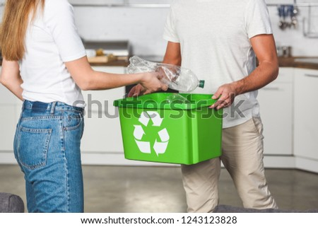 cropped view of woman putting empty plastic bottles in recycle green box