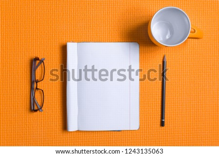 office desk table with book,pencil,glasses,glass ,orange black ground  #1243135063