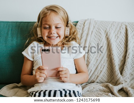 Little girl watching cartoons on her phone #1243175698