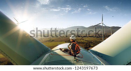 Happy engineer feel success after good work. He standing a top of windmill and looking beautiful sunset landscape #1243197673