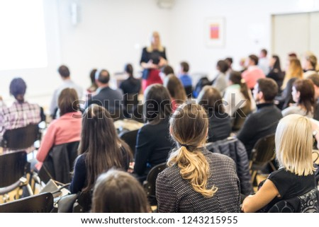 Business and entrepreneurship symposium. Female speaker giving a talk at business meeting. Audience in conference hall. Rear view of unrecognized participant in audience. Copy space on whitescreen. #1243215955