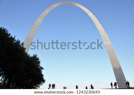 Gateway arch in St. Louis, with a clear blue sky in the background and silhouette of several unidentifiable people and a tree in the foreground, in evening. Concept of travel, places, monuments. #1243230643