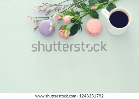 Top view image of white cup of coffee and colorful macaron or macaroon over pastel wooden background #1243231792
