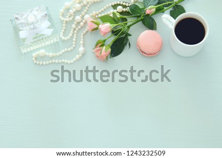 Top view image of white cup of coffee, perfume, white pearls and colorful macaron or macaroon over pastel wooden background #1243232509