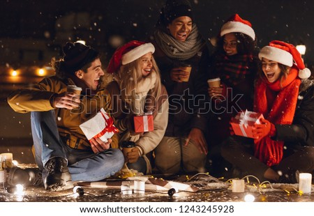 Photo of a happy young group of friends sitting outdoors in evening in christmas hats drinking coffee.