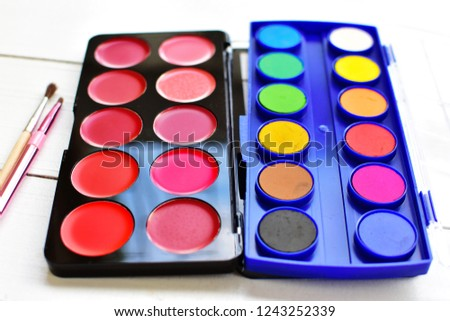 Colorful lipstick palette box and water color set palette box, comparing color during cosmetic and arts equipment with brush for lips and painting brush on white wooden isolated, beautiful art concept
