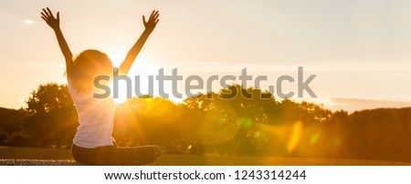 Panoramic web banner of mixed race African American girl teenager female young woman sitting on hay bale arms raised celebrating in sunset or sunrise golden evening or morning sunshine #1243314244