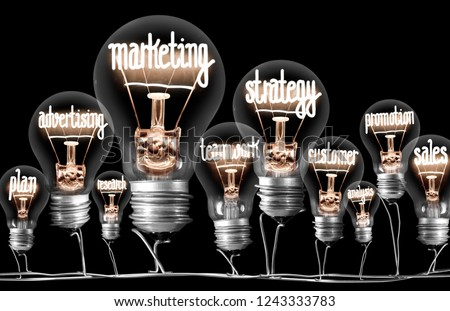 Photo of light bulbs with shining fibers in shapes of MARKETING concept related words isolated on black background #1243333783