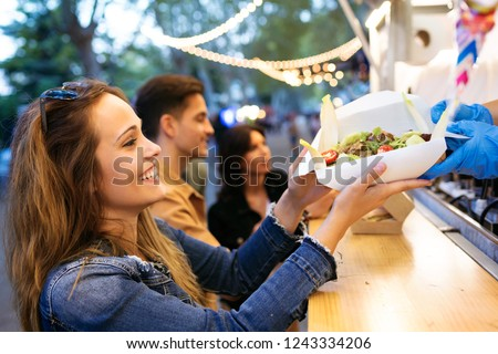 Shot of group of attractive young friends choosing and buying different types of fast food in eat market in the street. #1243334206