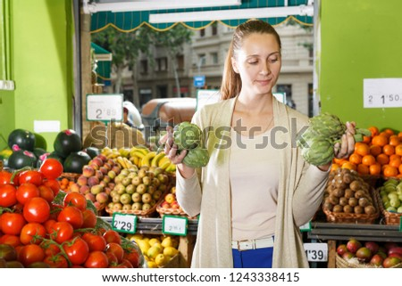 Portrait of woman who is standing with artichokes in the market. #1243338415