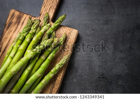 Asparagus. Fresh green asparagus on black slate background. Top view copy space. #1243349341