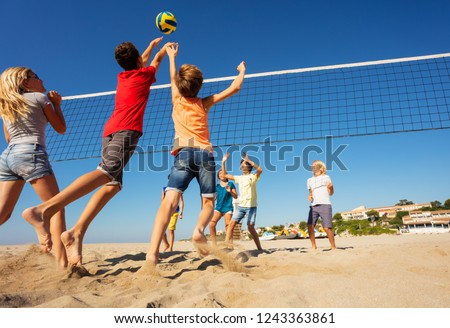 Beach volleyball players jumping to spike the ball #1243363861
