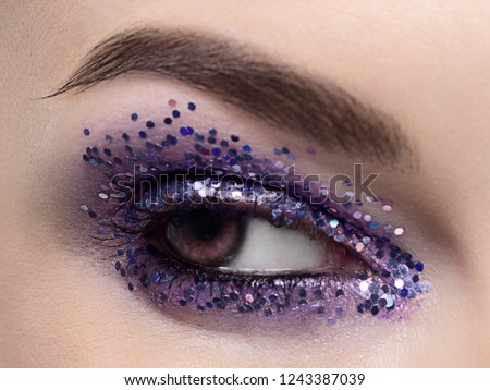 Beautiful macro shot of female eye with ceremonial makeup. Perfect shape of eyebrows, eyeliner and pretty blue sparkle on eyelid. Cosmetics and make-up. Closeup macro shot of fashion sparcle visage #1243387039