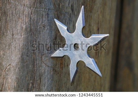 Shuriken (throwing star), traditional japanese ninja cold weapon stuck in wooden background #1243445551
