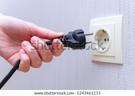 Ready to connect. Plugging electrical, black plug in electric socket on wall.  #1243461115