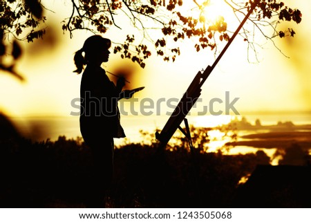 silhouette of a young woman drawing a picture with paints on an easel on nature, female standing under tree with brush and artist's palette engaged in art at sunset, concept leisure activity #1243505068