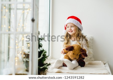 Little girl in the hat of Santa Claus with a plush deer sitting on the window. A child looks out the window and is waiting for Christmas, Santa Claus #1243591282