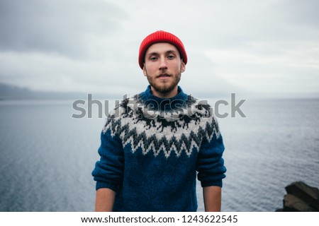 Young attractive bearded millennial man in red fisherman or sailor beanie hat and traditional icelandic ornament blue sweater stands on seaside on cloudy day, serious and tough personality #1243622545