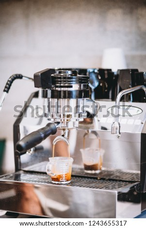Coffee beans being roasted at a cafe and being pulled by a barista into an espresso shot #1243655317