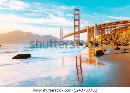 Classic panoramic view of famous Golden Gate Bridge seen from scenic Baker Beach in beautiful golden evening light on a sunny day with blue sky and clouds in summer, San Francisco, California, USA #1243739782