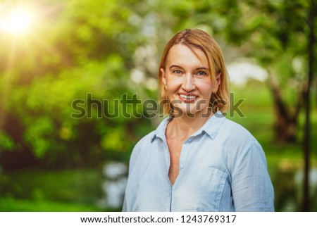 Portrait of happy middle aged woman standing in the park. The woman is smiling with happiness. #1243769317