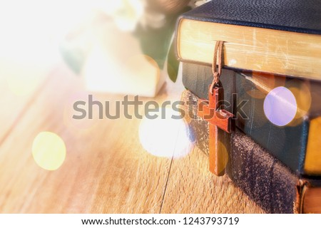 the wooden cross hanged on the bible on top of wood table at church with copy space, can be used for Christian concept or background