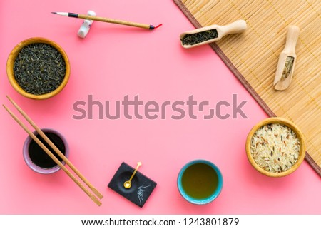 Chinese traditional symbols concept. Tea, rice, hieroglyph love, bambootabe mat, chopsticks, soy sause on pink background top view frame copy space #1243801879