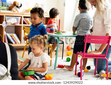Nursery children playing with teacher in the classroom Royalty-Free Stock Photo #1243929022