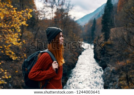 female tourist with a backpack near the river                      #1244003641