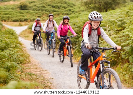 Pre-teen boy riding mountain bike with his sister and parents during a family camping trip, close up #1244019112