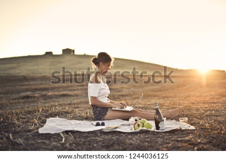 Pretty woman on a picnic using her laptop.
