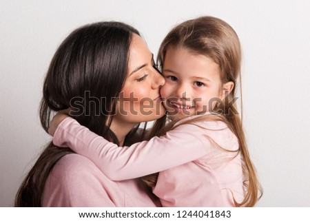 A close-up of a young mother kissing her small daughter in a studio.