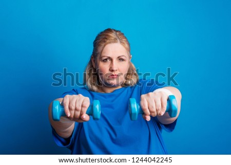 Portrait of a serious overweight woman with dumbbells in studio on a blue background. #1244042245