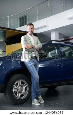 Man near new car in modern auto dealership #1244056051