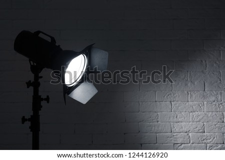 Professional photo studio lighting equipment near brick wall. Space for text #1244126920