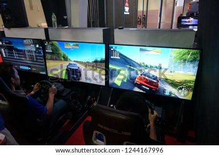 November 29, 2018 - KLIMS18, MALAYSIA. Local visitors including children were enjoying playing video games at Kuala Lumpur International Motorshow in Malaysia. #1244167996