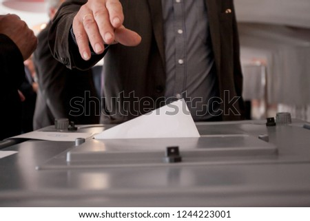 Hand of a person casting a vote into the ballot box during elections #1244223001
