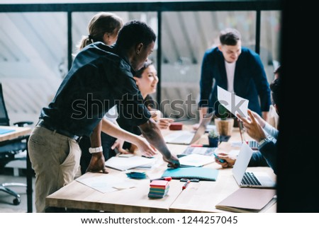 Multicultural team group of creative young people discussing business startup project at meeting table during brainstorming in modern office. Collaborative process of designers with productivity #1244257045