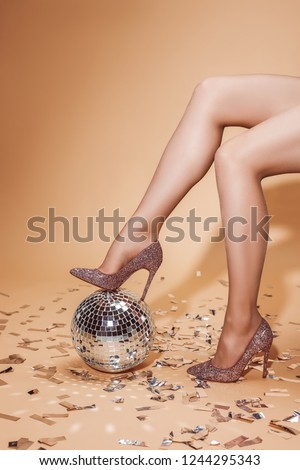 cropped image of woman in high heels putting leg on disco ball, beige floor with confetti Royalty-Free Stock Photo #1244295343