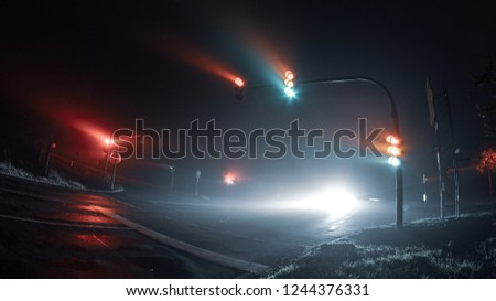 Thick fog over empty road with traffic light