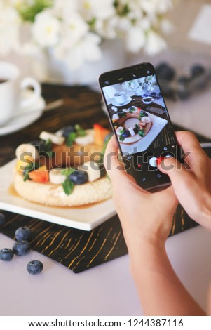 Food blogger taking picture of coffee mousse served with fruits and berries