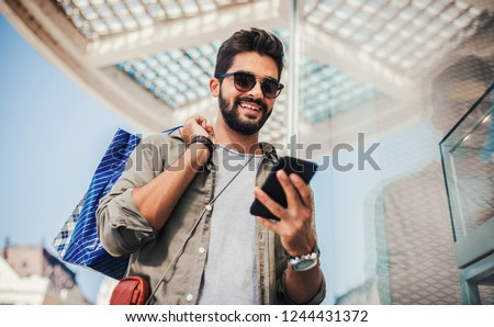 Man in shopping. Smiling man with shopping bags enjoying in shopping. Consumerism, shopping, lifestyle concept #1244431372