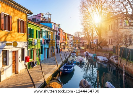Street with colorful buildings in Burano island, Venice, Italy. Architecture and landmarks of Burano, Venice postcard. Scenic canal and colorful architecture in Burano island near Venice, Italy #1244454730
