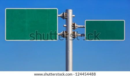 Blank green road sign board on blue sky