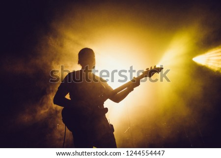 Guitarist silhouette on a stage in a smoke and backlights playing rock music Royalty-Free Stock Photo #1244554447