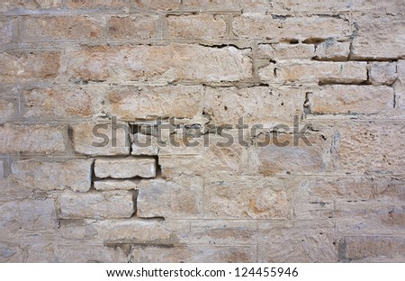 Detail of an old, crumbling stone wall.