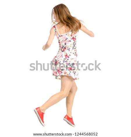 Beautiful woman in dress with flowers print and sneakers showing of positive emotions runs back view on white background isolation #1244568052