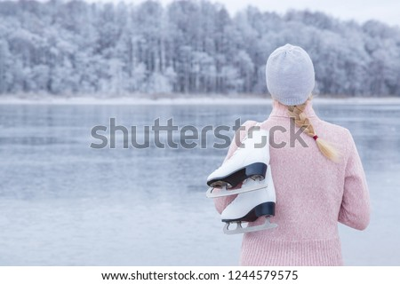 Young blond woman in pink sweater and hat staring at ice of lake and holding white skates over shoulder in freezing winter day. Back view of ice skater. Outdoor activities on weekends in cold weather.